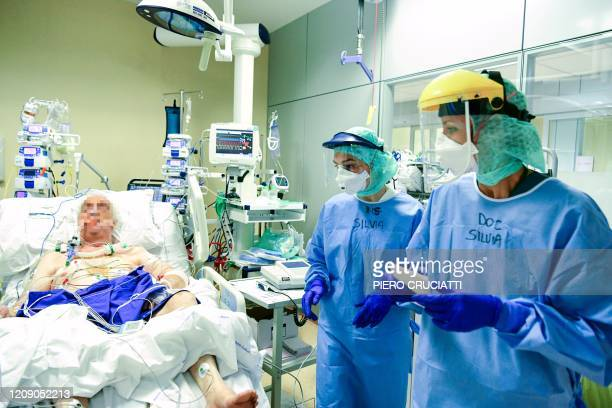 Members of the medical staff wearing their Personal Protective Equipment work examine a patient at the COVID-19 division at the ASST Papa Giovanni...