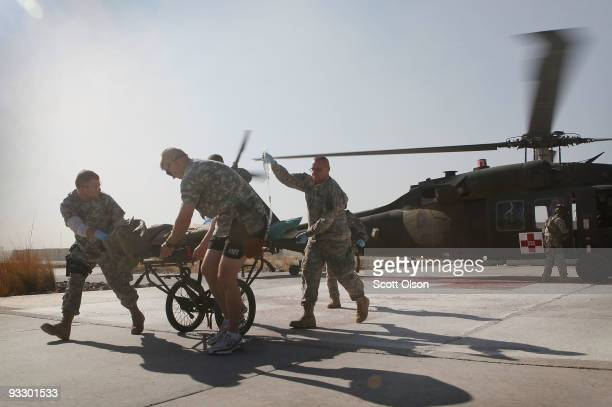 Members of the medical team from the 452nd Combat Support Hospital bring a wounded American soldier from a helicopter to the trauma unit at Sunday...