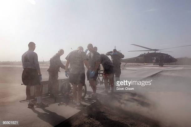 Members of the medical team from the 452nd Combat Support Hospital are hit with wash from the helicopter as they wait to offload a wounded American...