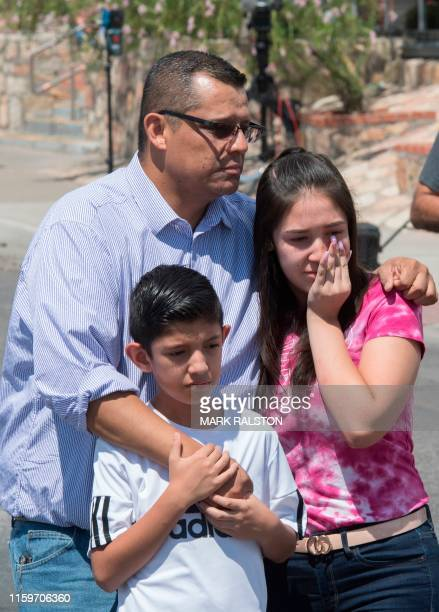 Members of the Medina family react beside a makeshift memorial outside the Cielo Vista Mall WalMart where a shooting left 20 people dead in El Paso...