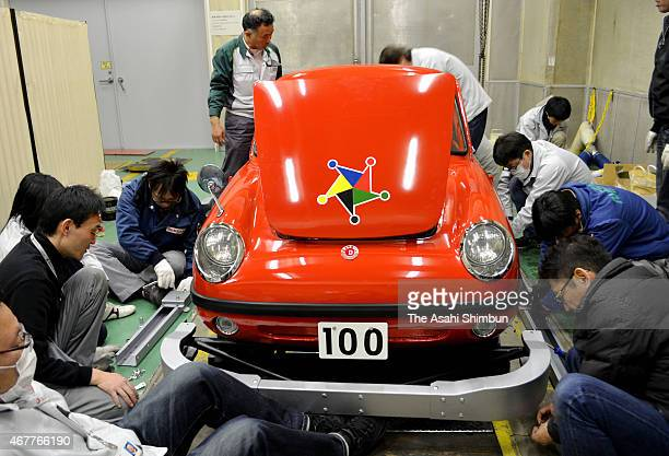 Members of the 'Meisha Saisei Club' of the Nissan Motor Co attach a bumper to the 'Datsun Baby' at the Nissan Technical Center on March 14 2015 in...
