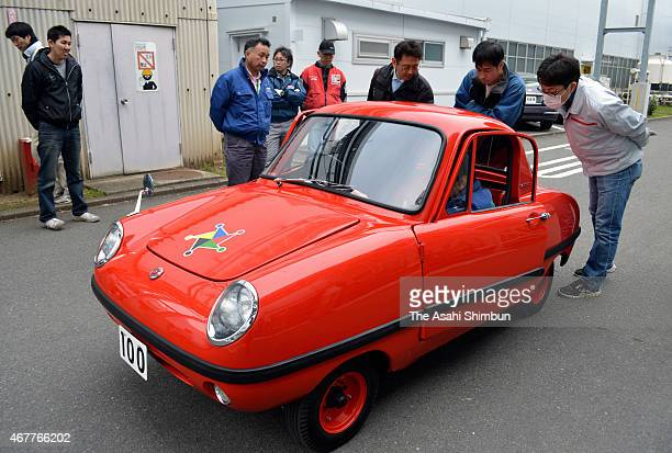 Members of the 'Meisha Saisei Club' of the Nissan Motor Co watch the 'Datsun Baby' at the Nissan Technical Center on March 14 2015 in Atsugi Kanagawa...