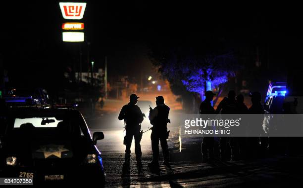 TOPSHOT Members of the Mexican Army and Federal police patrol a crime scene after an organized crime shooting at the Villa Juarez neighbourhood in...