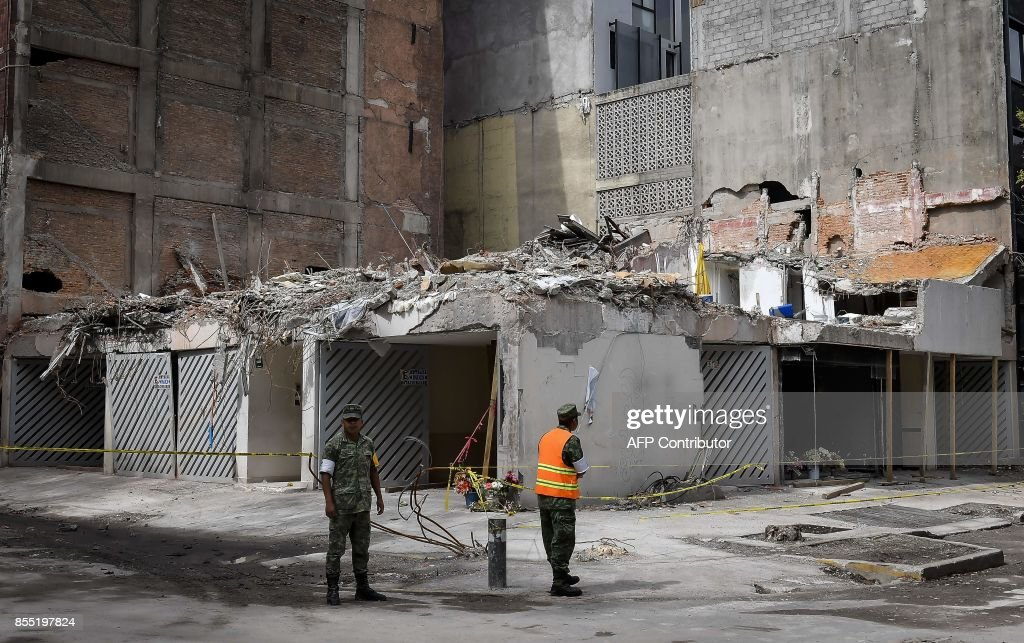 TOPSHOT - Members of the Mexican army guard one of the buildings destroyed during the September 19 earthquake, in one of Mexico City's most fashionable neighbourhoods on September 28, 2017. More than a week after an earthquake that killed more than 300 people, a shaken Mexico was torn between trying to get back to normal and keeping up an increasingly hopeless search for survivors. /