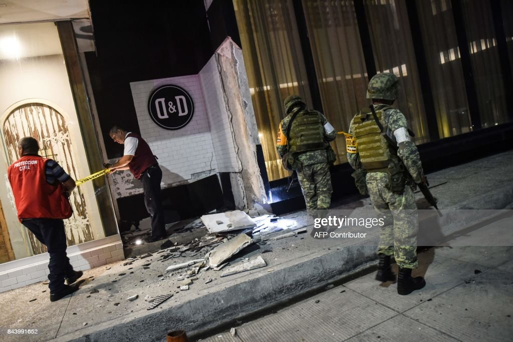 Members of the Mexican army look at damage caused by an earthquake in the Port of Veracuz on September 7, 2017. A rare and powerful 8.4-magnitude earthquake struck southern Mexico late on September 7, killing at least two people as seismologists warned of a tsunami of more than three meters (10 feet). / AFP PHOTO / Victoria RAZO
