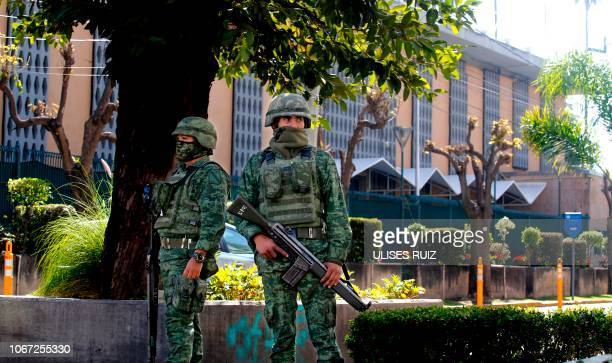 Members of the Mexican Army stand guard outside the US Consulate in Guadalajara Mexico on December 01 after an attack with an explosive device left a...