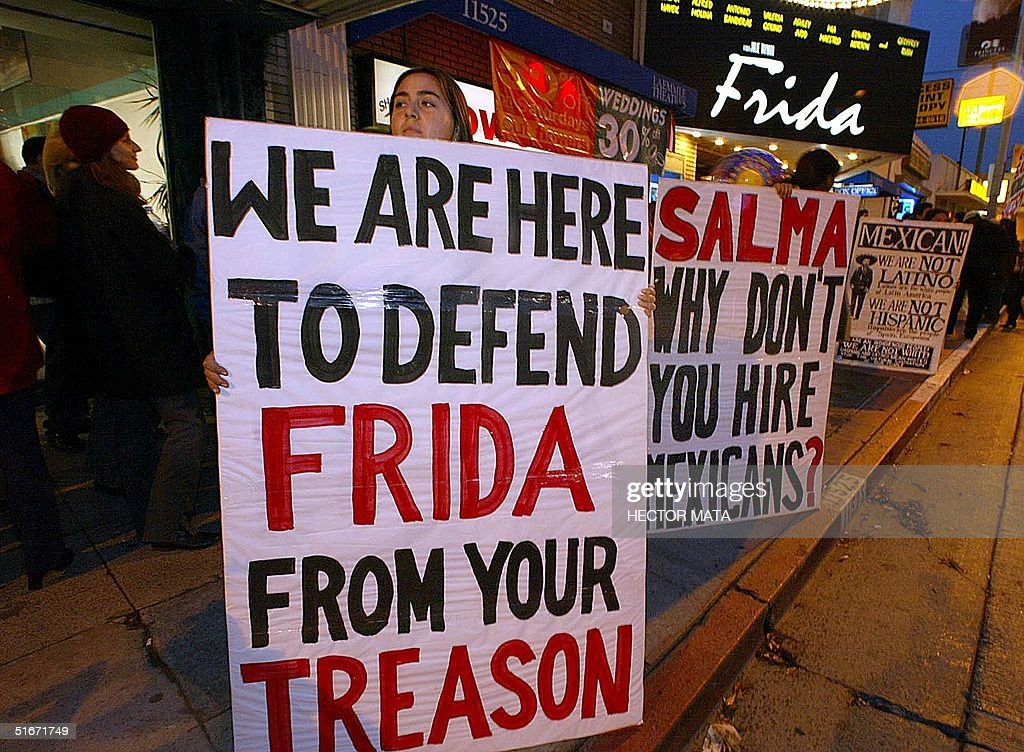 Members of the Mexican Movement hold signs outside a theater during the showing of the movie 'Frida' in West Los Angeles, 25 October 2002. The movement, an indigenous rights educational organization, demonstrate in front of the theater claiming that actress Salma Hayek who plays the role of Mexican painter Frida Kahlo and is also the producer of the film, refused to hire Mexican actors for the male leading roles. AFP PHOTO / Hector MATA
