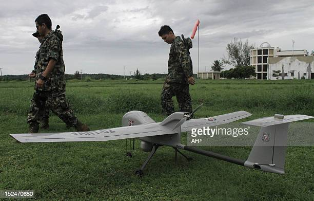 Members of the Mexican Navy make adjustments before a demo of a new drone at the Alvarado militar base in City port of Veracruz on August 27 2012 A...