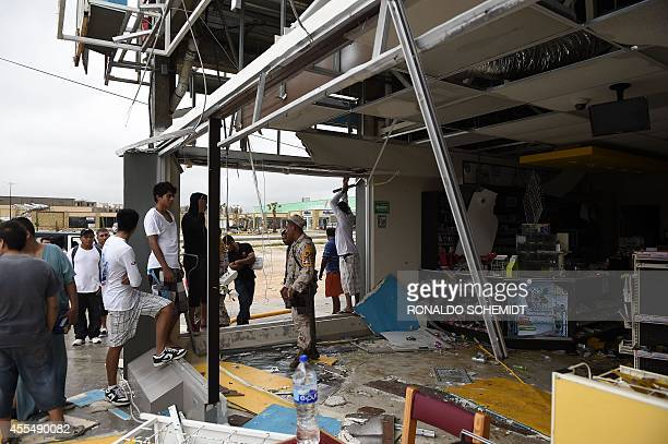 Members of the Mexican Navy stand guard at a looted supermarket in Cabo San Lucas on September 15 2014 after hurricane Odile knocked down trees and...