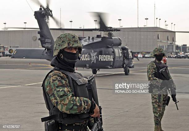 Members of the Mexican Navy stand guard next to a helicopter transporting Mexican drug trafficker Joaquin Guzman Loera aka 'el Chapo Guzman' on...