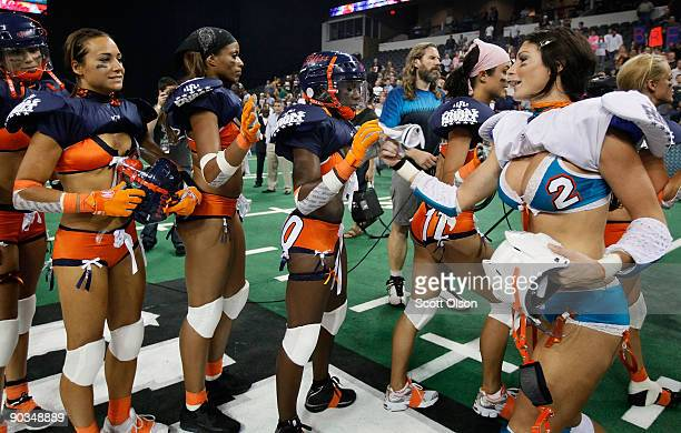 Members of the Miami Caliente and the Chicago Bliss high-five following the Bliss victory in the opening game of the Lingerie Football League at the...