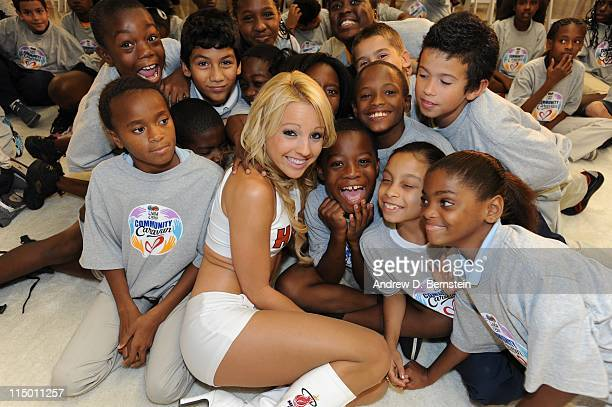 Members of the Miami Heat Dance Team pose with children during the unveiling of the Learn Play Center presented by HP and State Farm at the Paul...