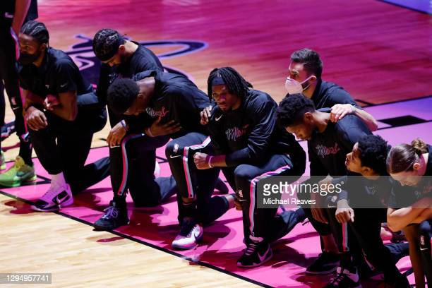 Members of the Miami Heat kneel during the playing of the national anthem prior to the game against the Boston Celtics at American Airlines Arena on...