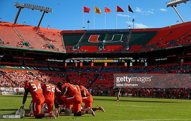 Members of the Miami Hurricanes wait out an injury during a game against the Virginia Cavaliers at Sun Life Stadium on November 23 2013 in Miami...