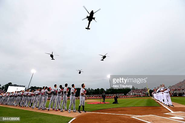 Members of the Miami Marlins and the Atlanta Braves are seen on the base paths during a military flyover prior to the game at Fort Bragg Stadium on...