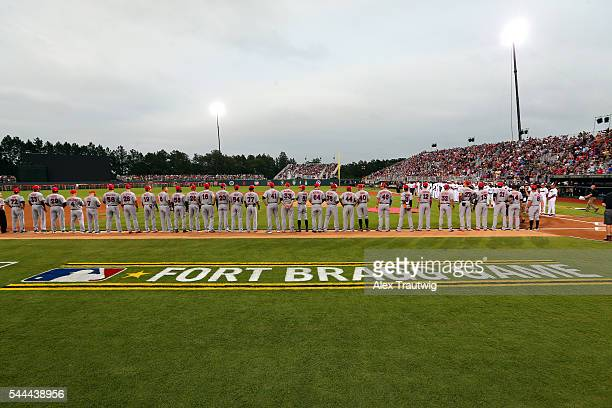 Members of the Miami Marlins are seen on the base path during the singing of the National Anthem prior to the game against the Atlanta Braves at Fort...