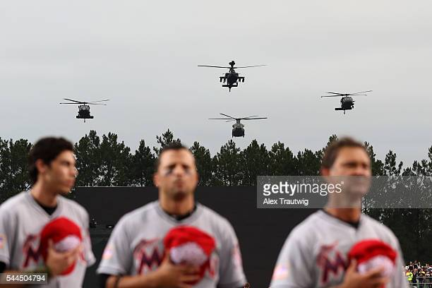 Members of the Miami Marlins are seen on the base path during the National Anthem as a military flyover takes place prior to the game against the...