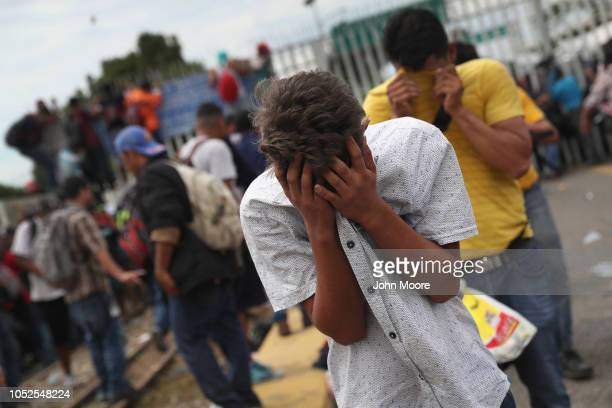 Members of the migrant caravan are overcome by tear gas fired by Mexican riot police on the border between Mexico and Guatemala on October 19 2018 in...