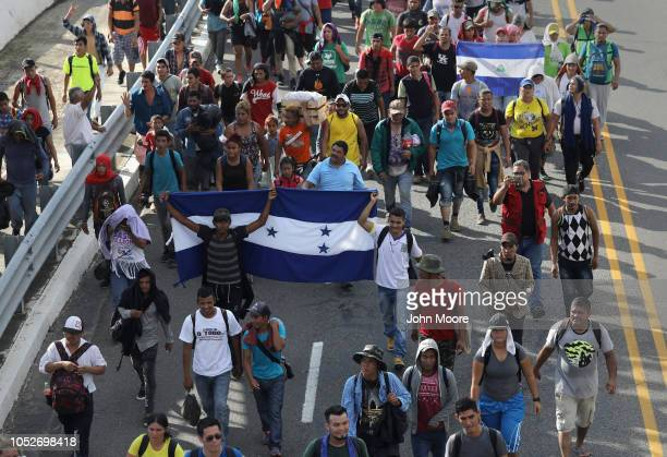 Members of the migrant caravan carrying flags of Honduras and Nicaragua while walk after crossing the Guatemalan border into Mexico on October 21...