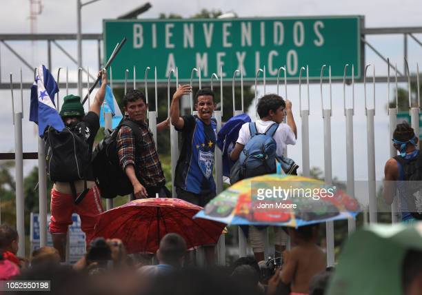 Members of the migrant caravan climb atop a gate during a clash with Mexican riot police on the border between Mexico and Guatemala on October 19,...