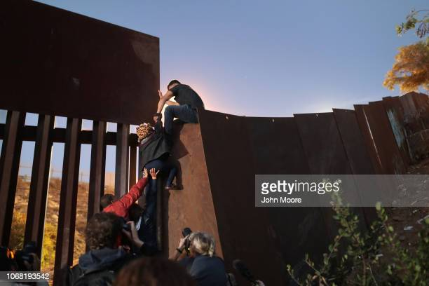 Members of the migrant caravan climb over the USMexico border fence on December 3 2018 while crossing into San Diego CA from Tijuana Mexico Many had...