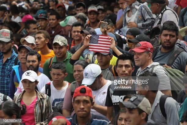 Members of the migrant caravan push forward at a gate separating Guatemala from Mexico on October 19 2018 in Ciudad Tecun Uman Guatemala The caravan...