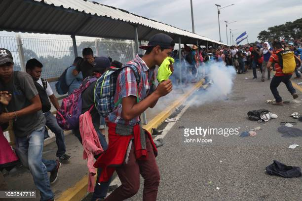 Members of the migrant caravan run from tear gas fired by Mexican riot police on the border between Mexico and Guatemala on October 19 2018 in Ciudad...