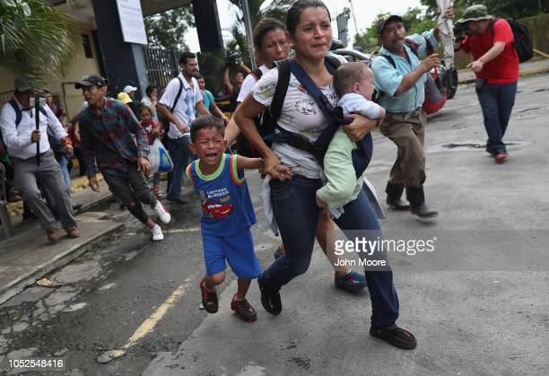 Members of the migrant caravan rush onto the bridge between Guatemala and Mexico after pushing past Guatemalan police a on October 19 2018 in Ciudad...