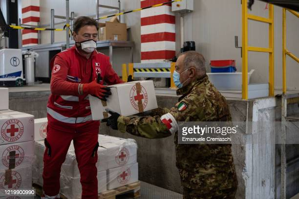 Members of the Milan Committee of the Italian Red Cross and of the Military branch of the Italian Red Cross load boxes of food which will be...