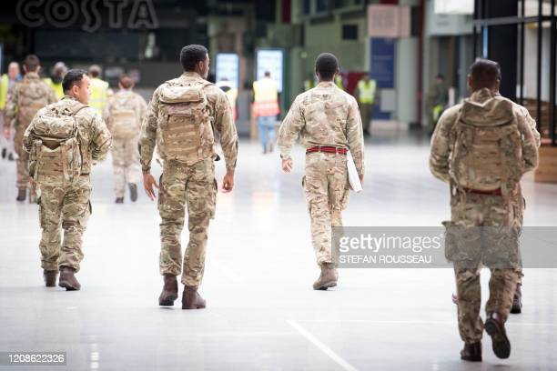 Members of the military and private contractors help to prepare the ExCel centre in London on March 30 which has been transformed into a field...