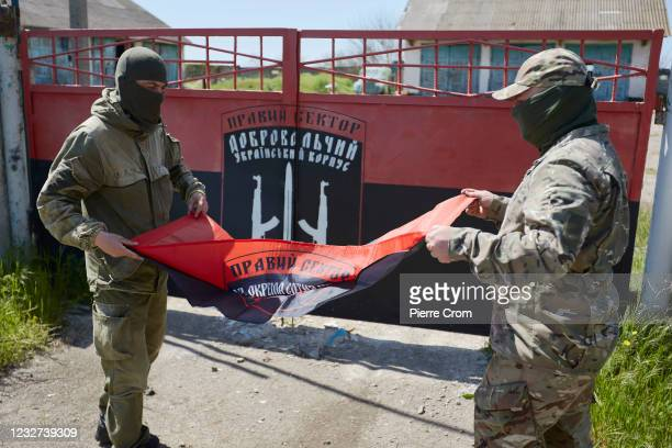Members of the military branch of Ukrainian nationalist militia Right Sector fold a flag outside their base on May 6, 2021 in Chonhar, Ukraine....