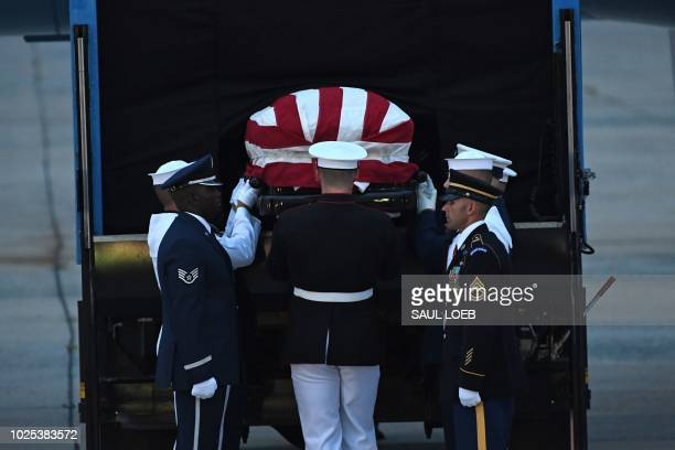 Members of the military carry the flagdraped casket of the late US Senator John McCain Republican of Arizona after arriving on a military airplane at...