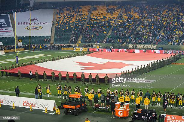 Members of the Military hold a Canadian flag during the singing of the national anthem prior to a CFL game between the Edmonton Eskimos and the...