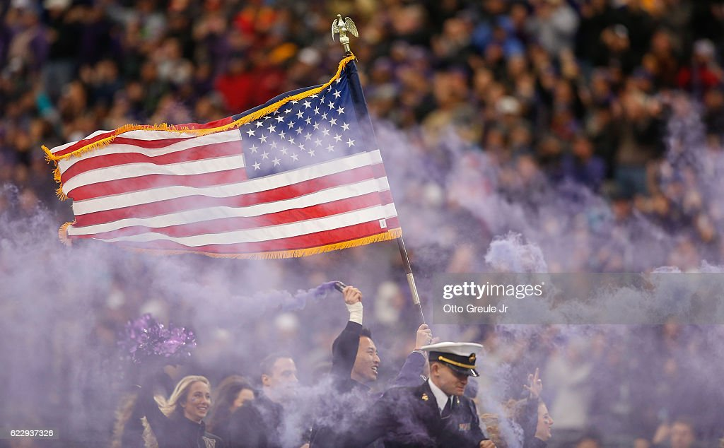 Members of the military run onto the field along with Husky cheerleaders prior to the game between the USC Trojans against the Washington Huskies on November 12, 2016 at Husky Stadium in Seattle, Washington. The Trojans defeated the Huskies 24-13.