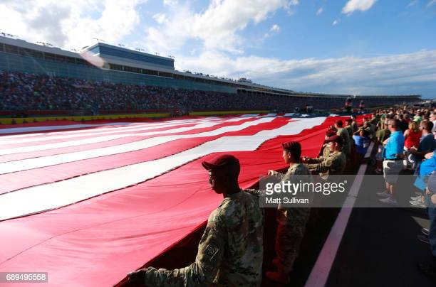 Members of the military stand at attention prior to the Monster Energy NASCAR Cup Series CocaCola 600 at Charlotte Motor Speedway on May 28 2017 in...