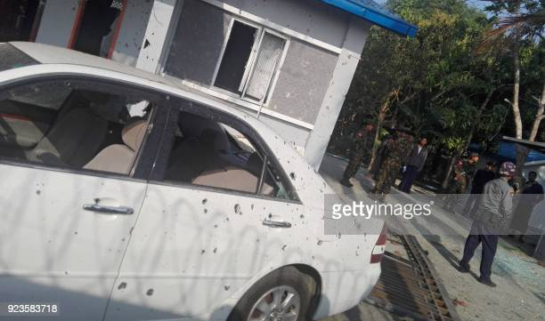 Members of the military stand guard next to a damaged car after an early morning explosion in the compound of the state government secretary's home...