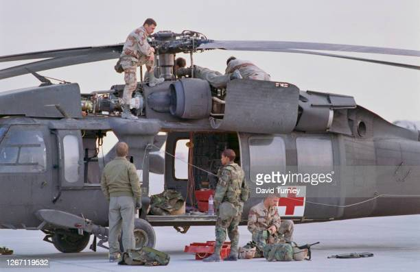 Members of the military with a Sikorsky UH-60 Black Hawk helicopter, with a red cross on the open side door during the liberation of Kuwait following...