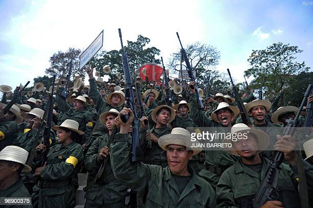 Members of the militia raise up their rifles before a speech of Venezuelan President Hugo Chavez in Caracas on February 20 2010 Chavez will propose...