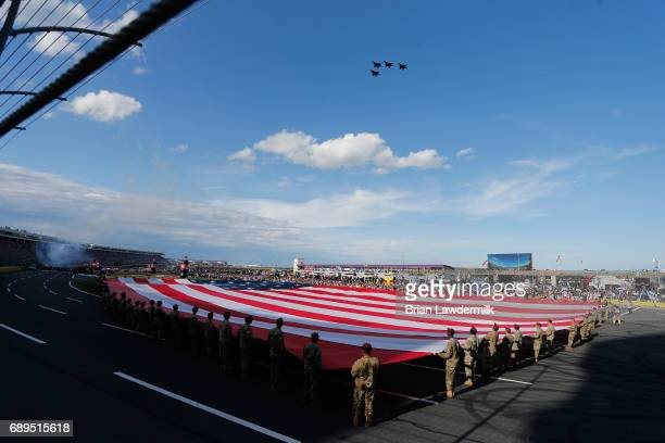 Members of the miltary hold the flag during the national anthem before the Monster Energy NASCAR Cup Series CocaCola 600 at Charlotte Motor Speedway...