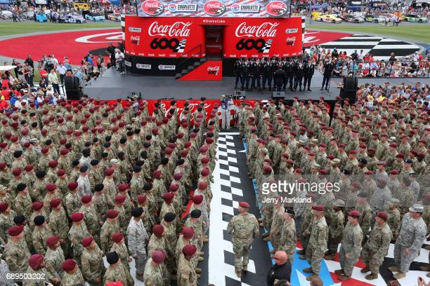 Members of the miltary stand at attention prior to the start of the Monster Energy NASCAR Cup Series CocaCola 600 at Charlotte Motor Speedway on May...