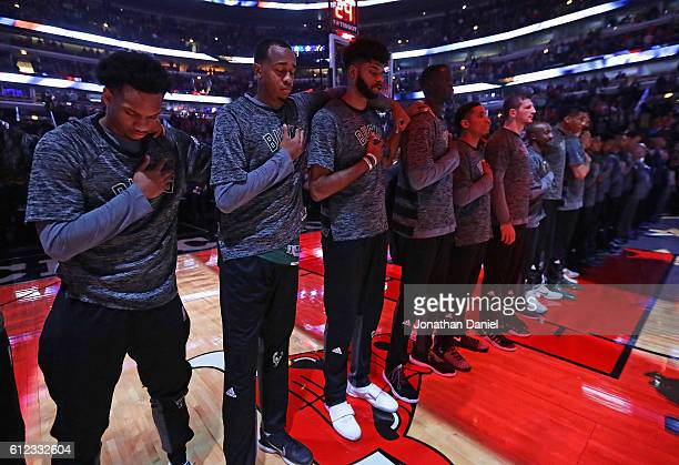 Members of the Milwaukee Bucks stand with their arms around her others shoulders as a sign of solidarity during the National Anthem before a...