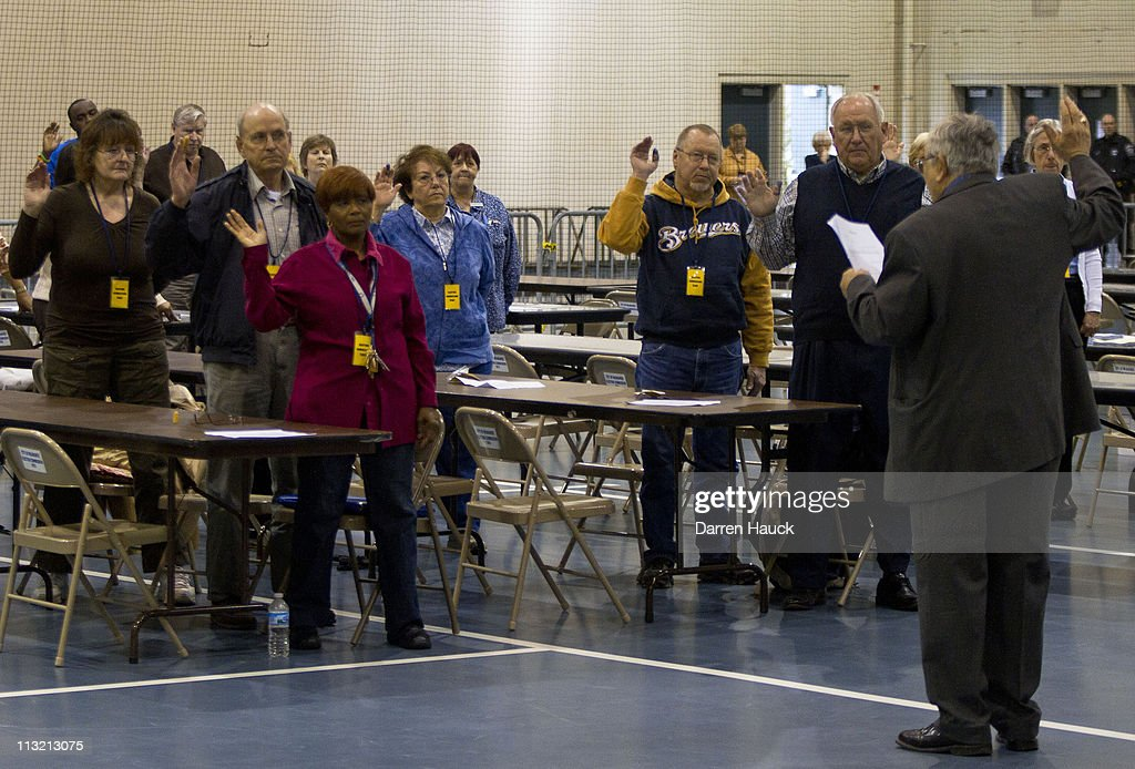 Members of the Milwaukee County Election Commission are sworn in before they recount the ballots for the Wisconsin Supreme Court race between incumbent Justice David Prosser and Assistant Attorney General JoAnne Kloppenburg at the Milwaukee County Sports Complex on April 27, 2011 in Milwaukee, Wisconsin. Observers from the Prosser and Kloppenburg campaign were overseeing the process to validate the recount.