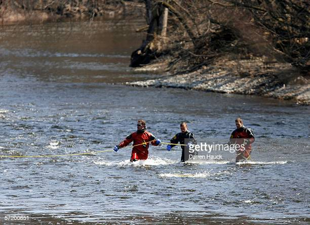 Members of the Milwaukee police department dive team wade through water along the banks of the Milwaukee River in search for missing boys Quadrevion...