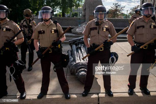Members of the Minnesota State Patrol stand guard over a statue of Christopher Columbus which was toppled to the ground by protesters on the grounds...