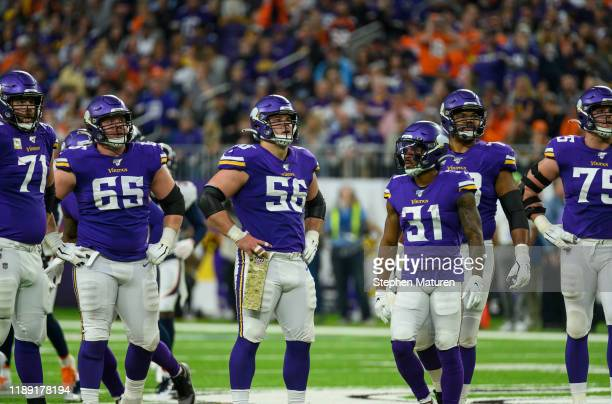 Members of the Minnesota Vikings offensive line watches a replay in the third quarter of the game against the Denver Broncos at US Bank Stadium on...