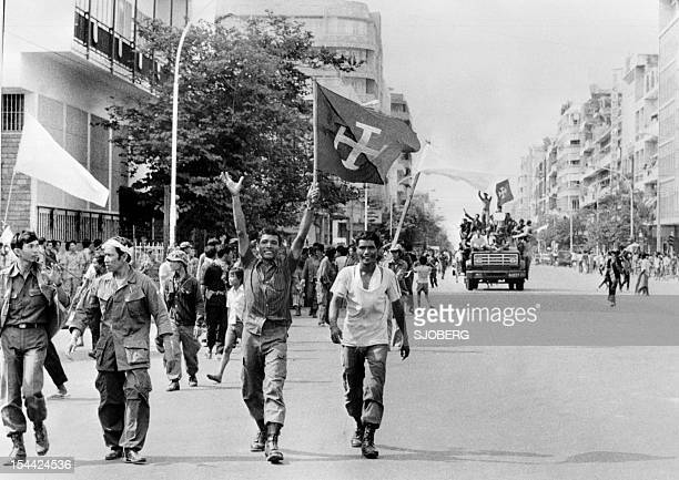 Members of the MONATIO group wave flags 17 April 1975 as they enter Phnom Penh the day Cambodia fell under the control of the Communist Khmer Rouge...