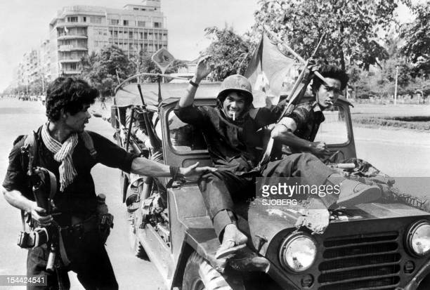 Members of the MONATIO group wearing black uniforms drive 17 April 1975 atop jeeps through a street of Phnom Penh the day Cambodia fell under the...