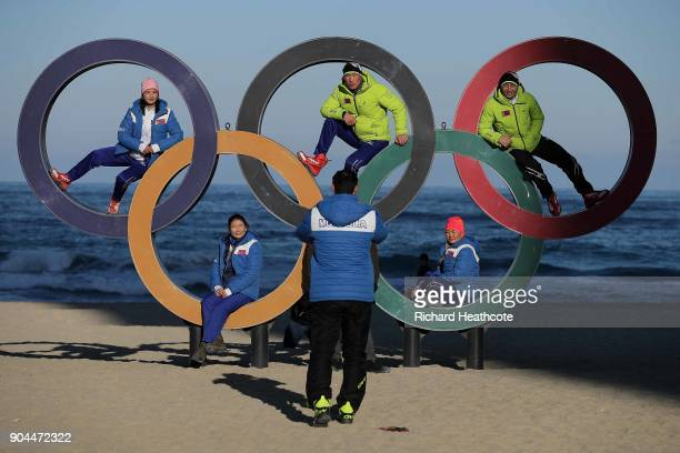 Members of the Mongolian ski team take selfies with the Olympic Rings on the beach at Gangneung ahead of the Pyeongchang 2018 Winter Olympics on...