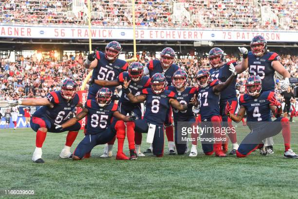 Members of the Montreal Alouettes pose after teammate and quarterback Vernon Adams Jr. #8 scores a touchdown in the first quarter against the Ottawa...