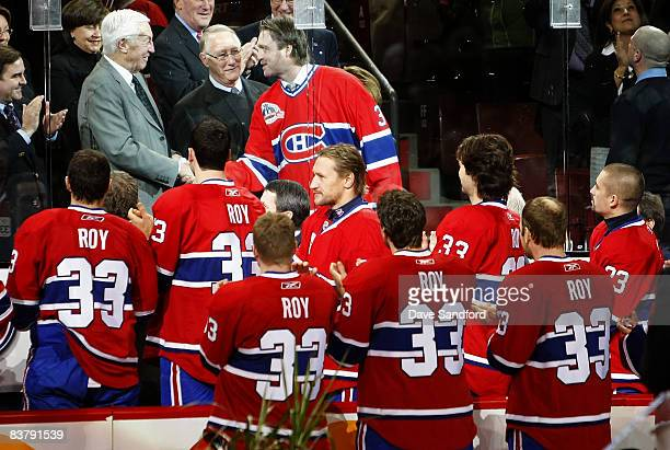 Members of the Montreal Canadiens look on as Patrick Roy shakes hands with Jean Beliveau as the Montreal Canadiens honoured Patrick Roy by retiring...